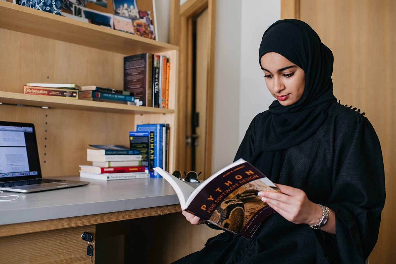 A student reading a book inside her residential college suite.