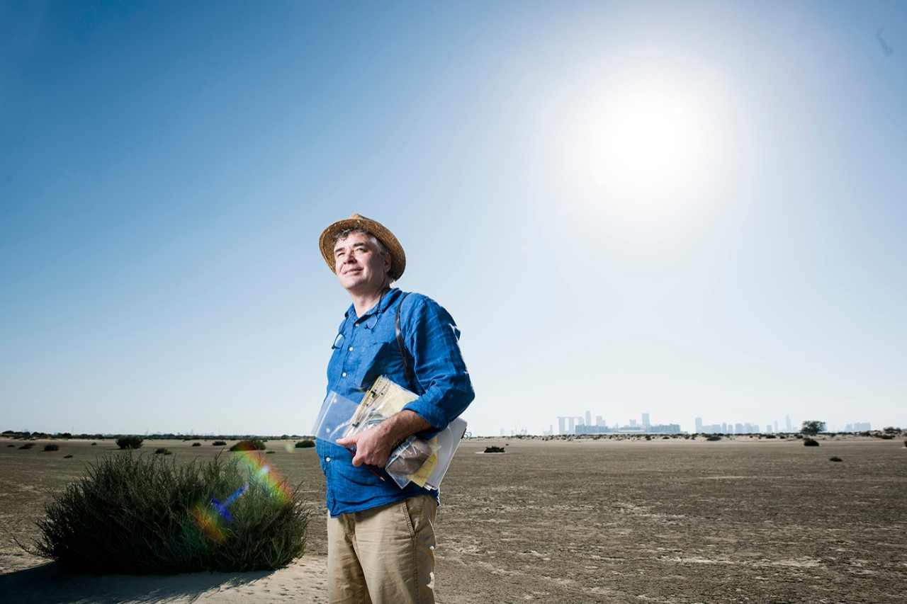 Director of the NYU Abu Dhabi Dhakira Center for Heritage Robert Parthesius stands in the desert outside Abu Dhabi.