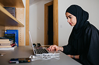 NYUAD student working on her laptop