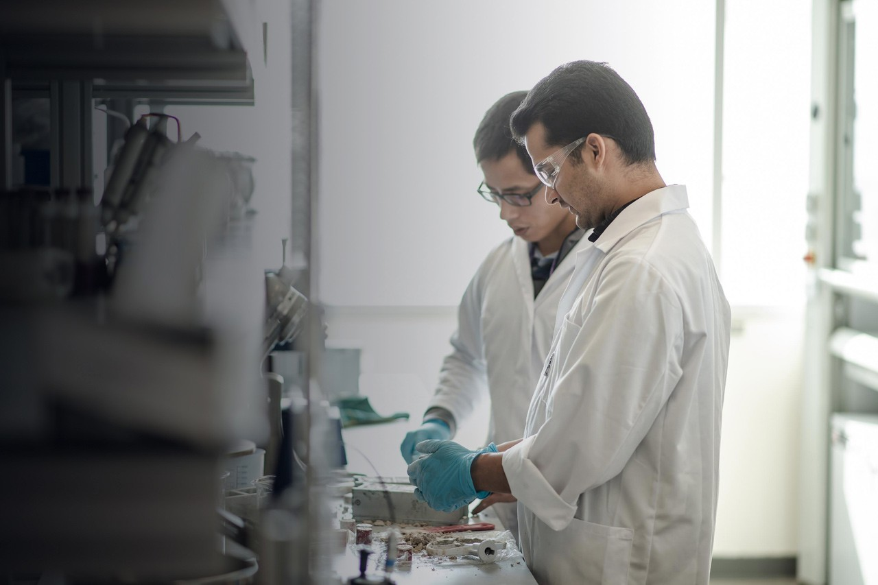 Two scientists in a lab working on a cement mixture.