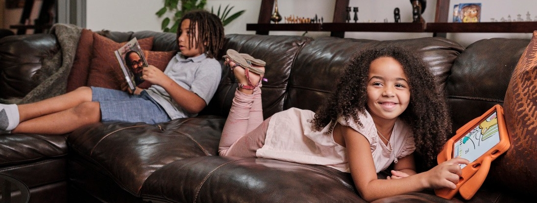 Two children relaxing on a sofa.