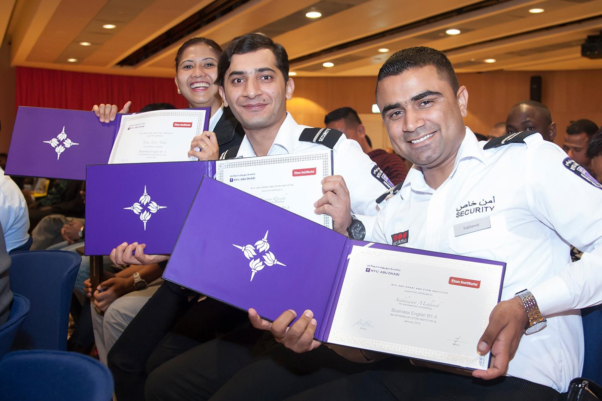 A trio of proud NYUAD security guards show off their newly earned adult education certificates.