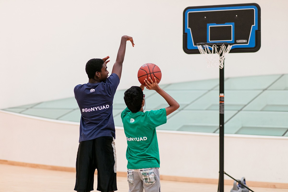 Student playing a game of basketball during a special needs volunteer program.