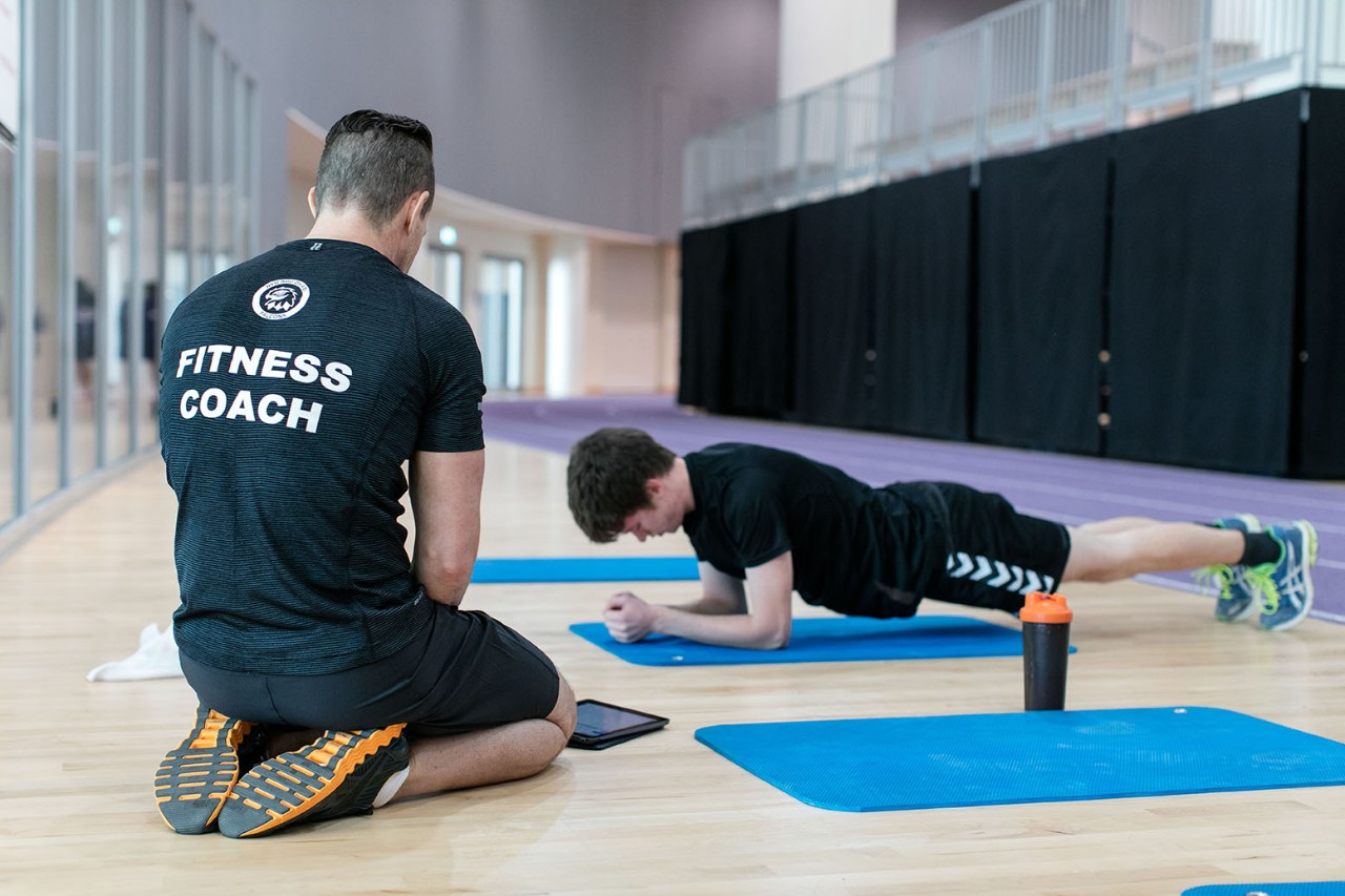 A fitness coach and student during a personal training session.