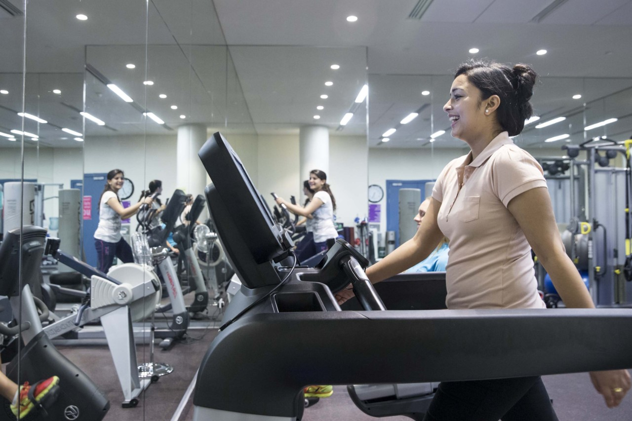 A female gym user using the treadmill in the ladies-only fitness room.