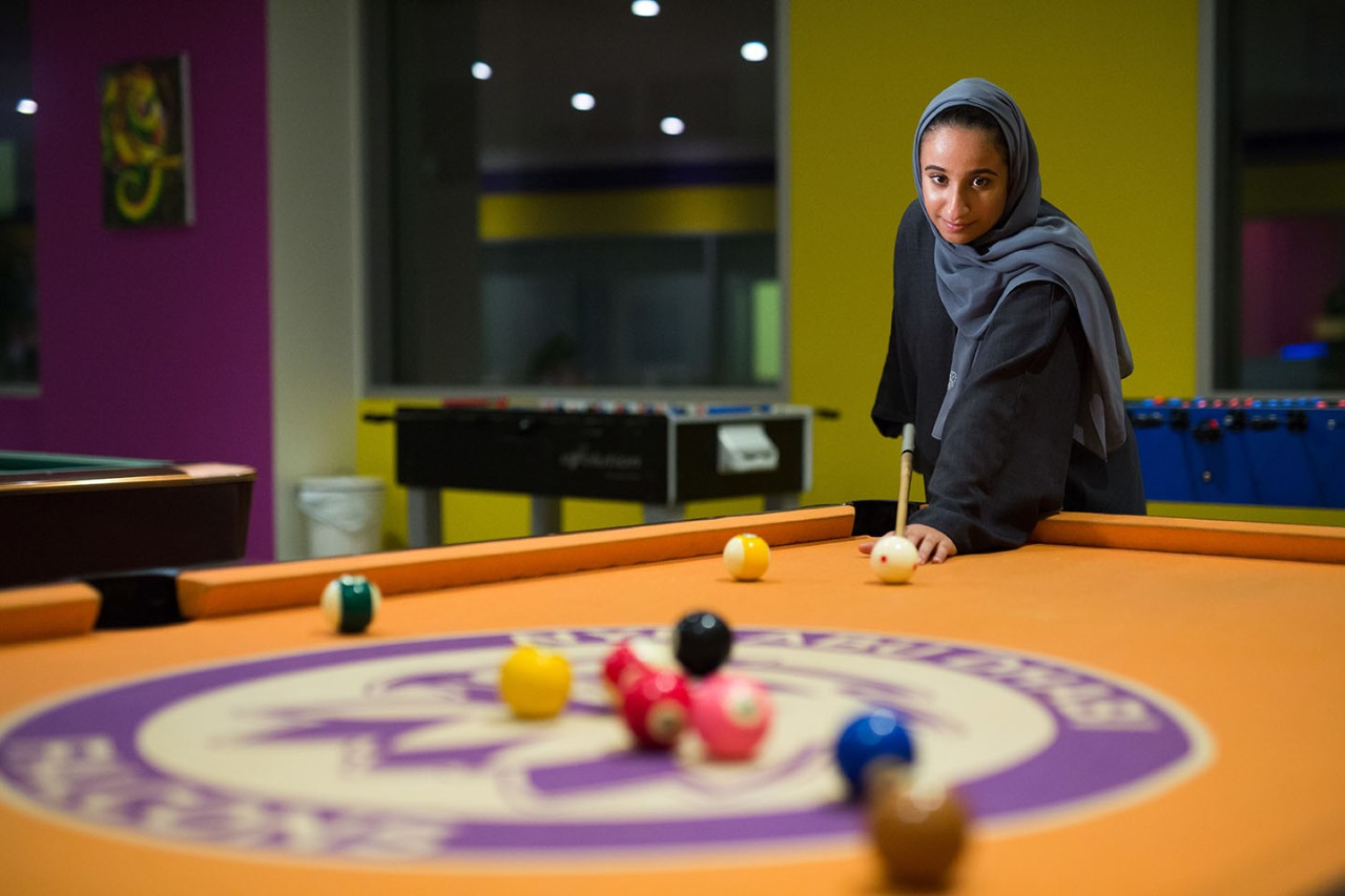 Student enjoying a game of pool in the Baraha area.
