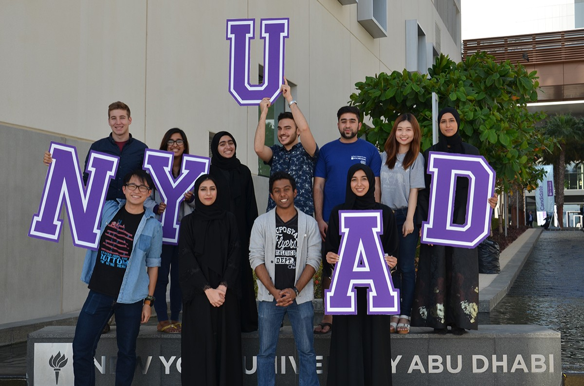 Students posing with a NYUAD sign on campus.
