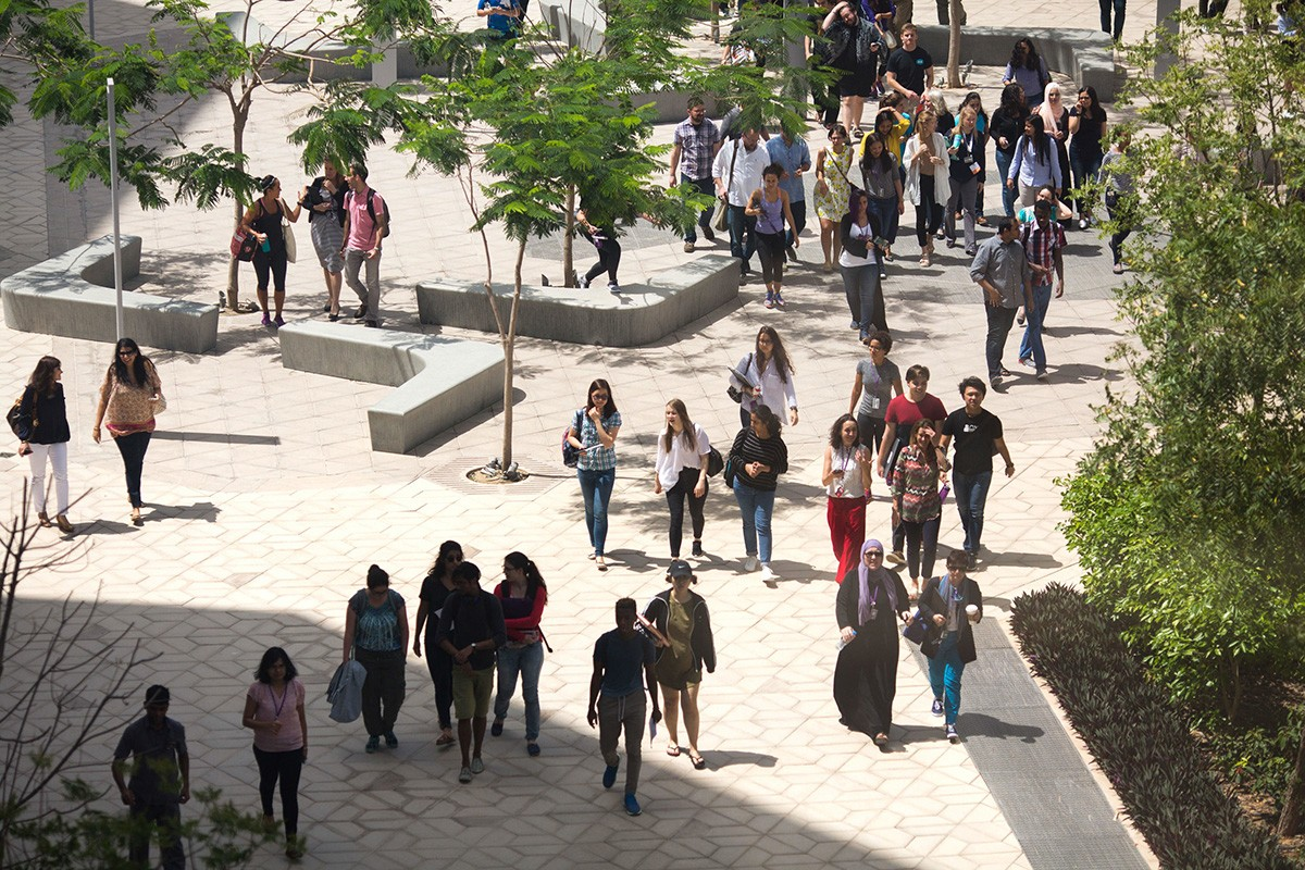 People walk through NYU Abu Dhabi's campus