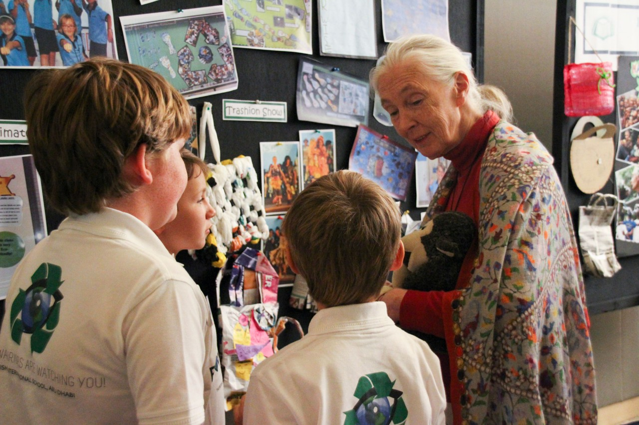 Jane Goodall talking to three young students.