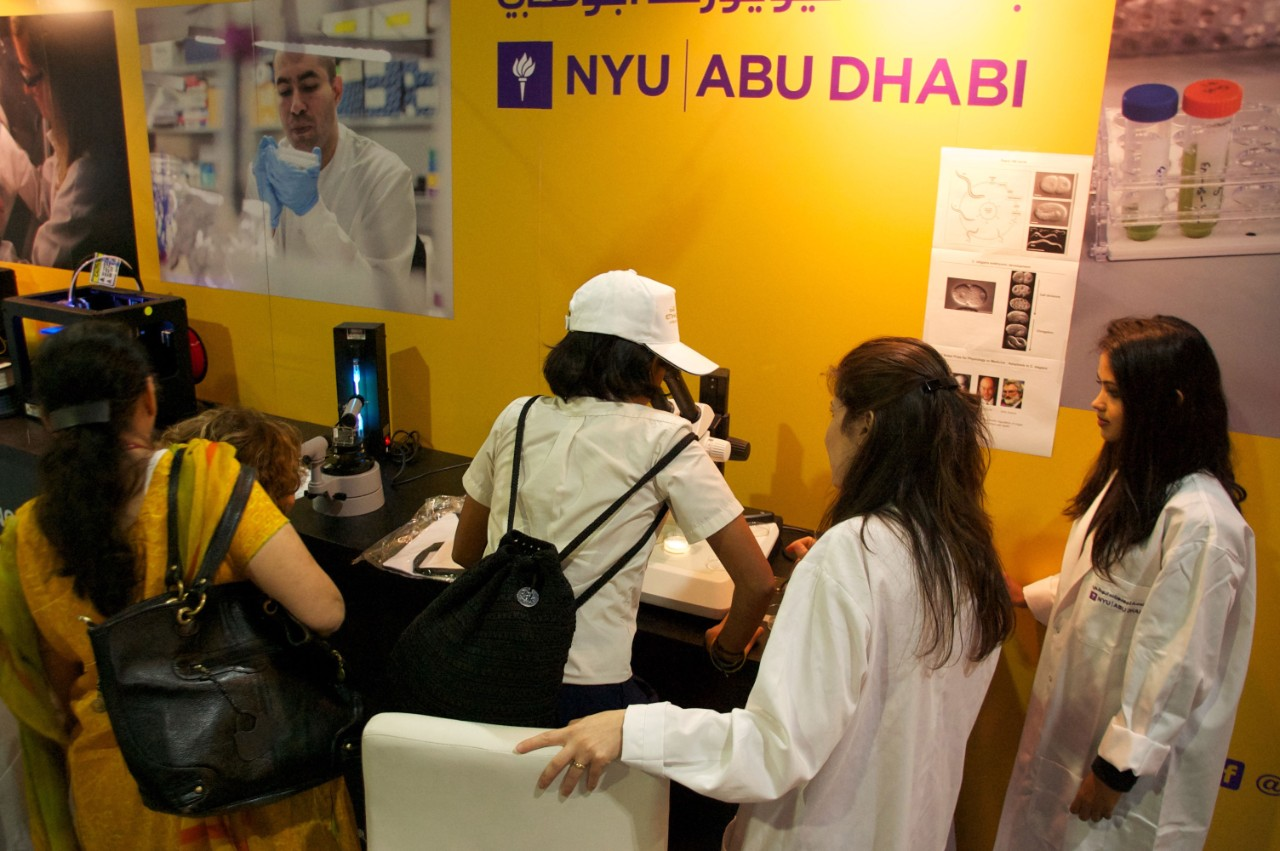 Students investigate microscopic samples at the NYUAD Think Science fair exhibit.