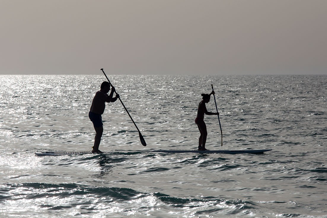 Two people on a stand up paddle board in Saadiyat Beach.
