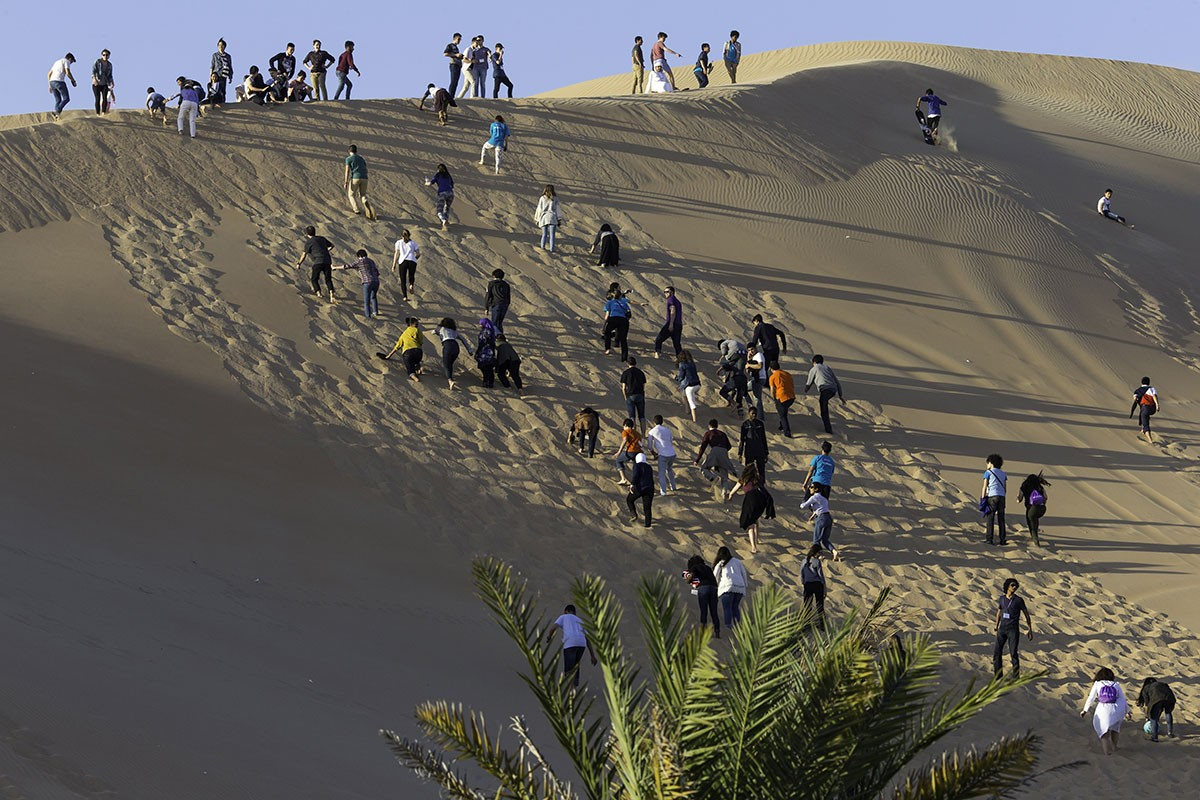 Students climb a sand dune in the UAE desert.
