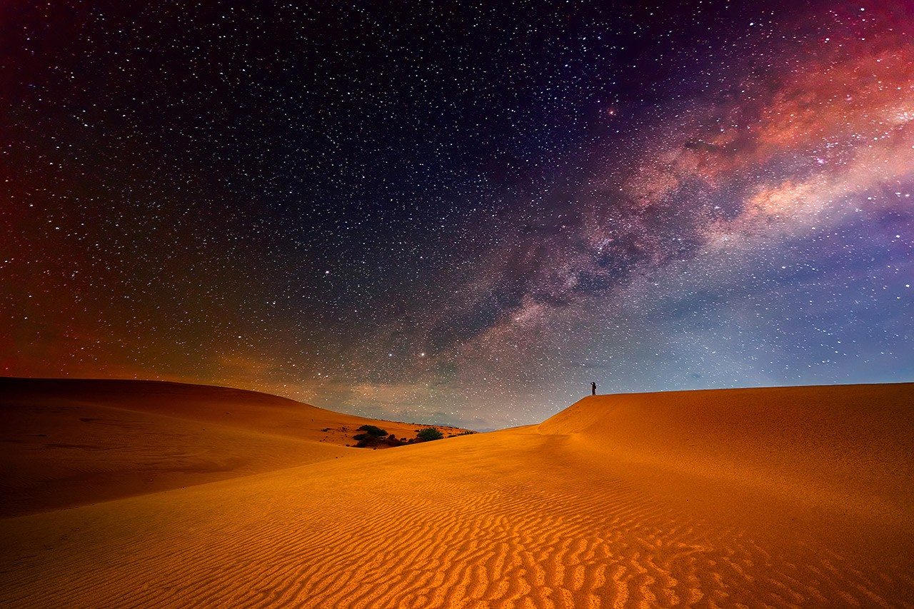 Figure stands on a hill in the desert, looking at the starry sky.