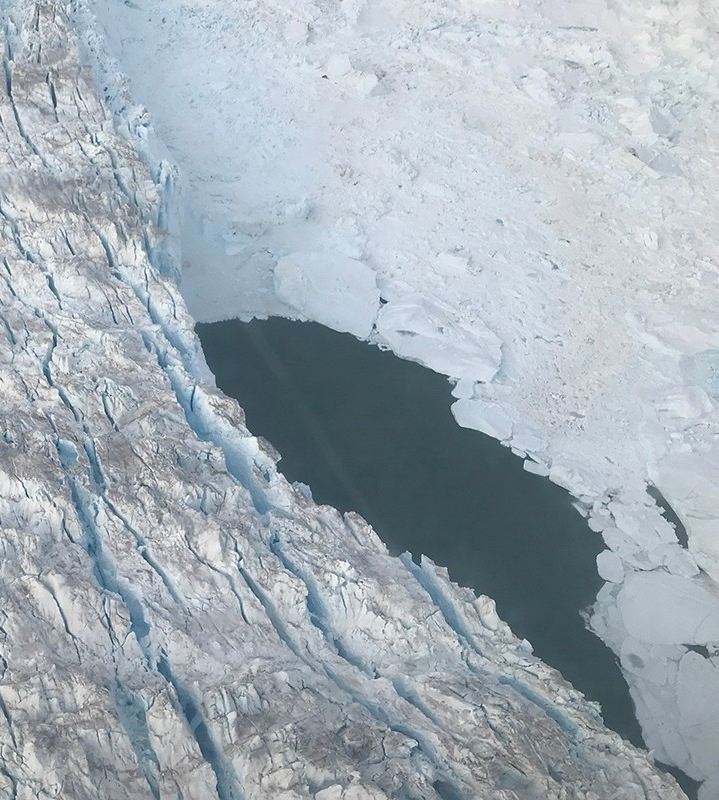 August 5th, 2019.  Researchers from NYU New York and Abu Dhabi identify an unexpected and large opening in the melange at the calving front of the Helheim Glacier. A temperature probe was deployed and results showed a uniform temperature of approximately 4 degree centigrade from top to bottom. Image credit: Denise Holland, NYU Abu Dhabi Center for Global Sea Level Change.