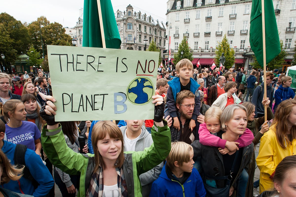 "A sign reads, ""There Is No Planet B"", as parents carry children among thousands marching through central Oslo, Norway, to support action on global climate change. iStock"