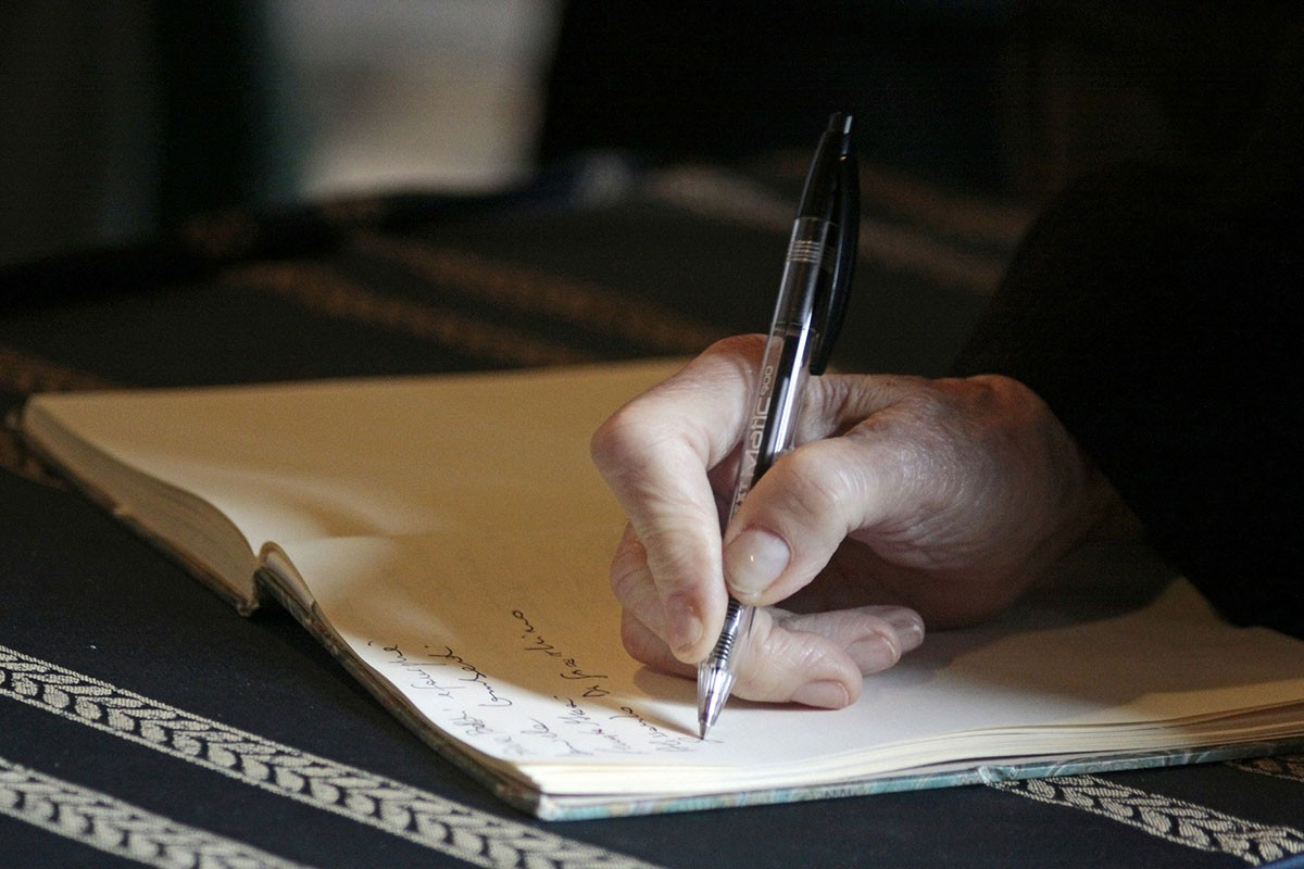 A person writing in a note book with a pen.