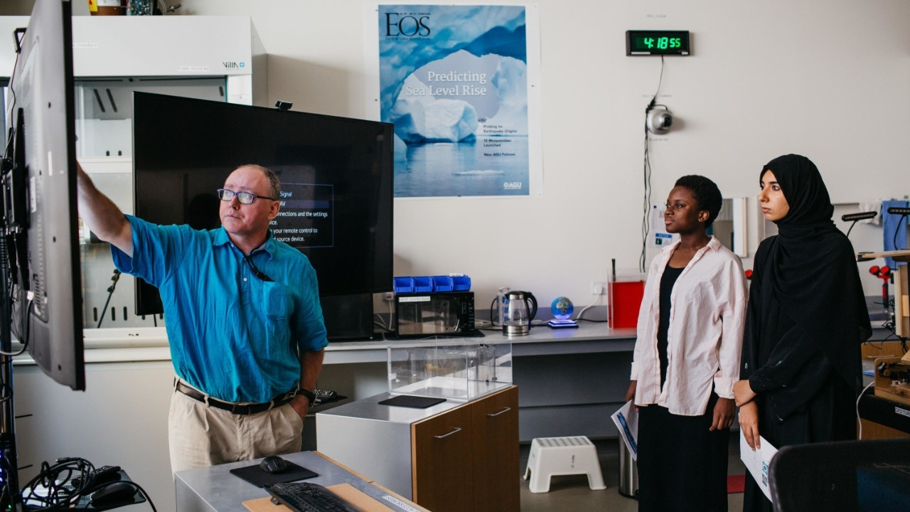 Math professor David Holland instructs two students in the Center for Sea Level Change at NYU Abu Dhabi.